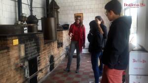 La guia explica el funcionament de l'alambí durant una de les visites a la Destil·leria